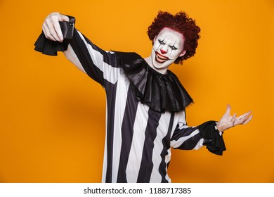 Horrific clown man 20s wearing black costume and halloween makeup taking selfie photo on mobile phone isolated over yellow background