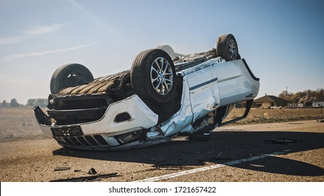 Horrific Traffic Accident, Rollover Smoking and Burning Vehicle Lying on its Roof in the Middle of the Road after Collision. Daytime Crash Scene with Severely Damaged Car.
