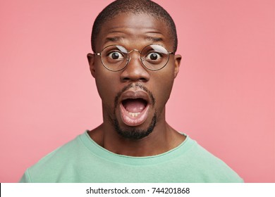 Horrified dark skinned bald man keeps mouth widely opened, poses agianst pink wall, being shocked with terrified news or big sales in shoping mall. People, emotions and facial expressions concept