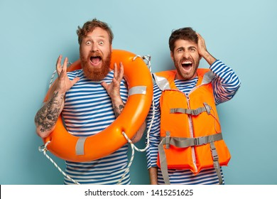 Horrified emotional rescurers work on beach as lifeguards, holds lifebelt, wears orange protective vest, shout from panic as swimmer drowns, needs help, yell oh no. Lifesaving and safe rest concept