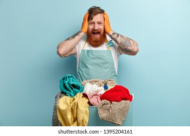 Horrified ginger young man keeps hands on head, opens mouth widely, wears casual blue basin, overstained with housekeeping, stands in front of basin with laundry. Annoyed male householder indoor