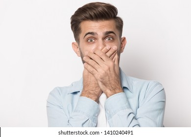 Horrified millennial man covering mouth with hands looking at camera head shot portrait isolated on grey studio background, guy big eyes feeling scared afraid fear awe face expressions concept image