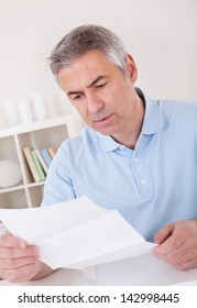 Horrified old man reading a document with an aghast expression.