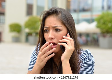 Horrified upset young woman talking on a mobile phone raising her hand to her lips in a natural gesture outdoors on an urban street