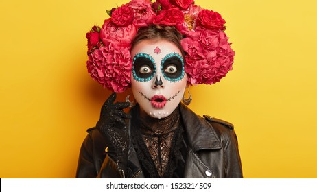 Horrified woman with painted skull on face, dressed in special costume during day of death to honour dead people, celebrates Mexican version of Halloween, holds breath from seeing something terrifying