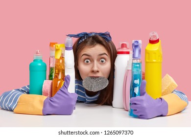 Horrified young female has eyes popped out, keeps sponge in mouth, embraces cleaning supplies, stupefied with much work about house, tired of cleaning kitchen, isolated over pink background.