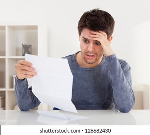 Horrified young man reading a document with an aghast expression and his hand to his forehead as he stares wide eyed at the page of paper