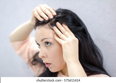 Horrified young woman looking in the bathroom mirror staring open mouthed at first grey hair on her scalp