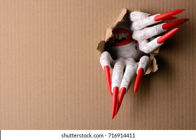 A horrifying vampire tearing a hole through cardboard with sharp red claws in a halloween horror theme with copy space.