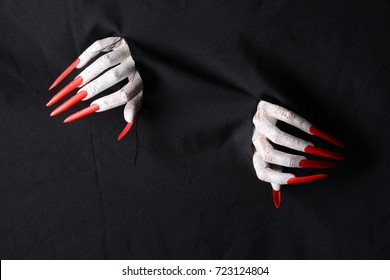 A horrifying vampire tearing a hole through black fabric with sharp red claws in a halloween horror theme.