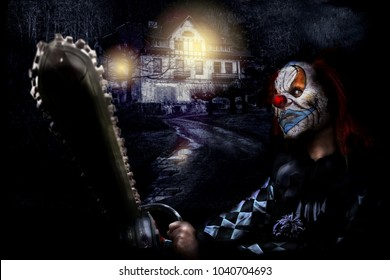 horror clown with chainsaw near scary house