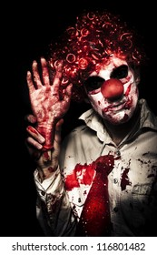 Horror Clown Waving Chopped Off Hand To Welcome You To A Evil Circus Act Of Terror On Black Background
