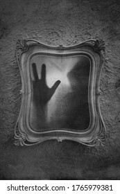 Horror concept of a ghostly figure trapped in a mirror. With a grunge, blurred, textured, black and white edit.