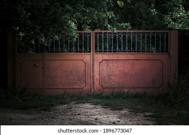 Horror concept. Iron scary rusty old closed metal gates with mystical shadows in a dark forest against the background of trees causing fear, the entrance to a gloomy cemetery in the park