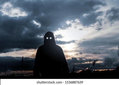 A horror concept. A silhouette of a hooded figure, standing in a field, , with scary glowing eyes looking at the camera. Back lighted by the setting sun.