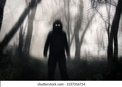 A horror concept. A silhouetted hooded figure, standing in a winter forest, with glowing scary eyes. With a grunge, texture, blurred edit