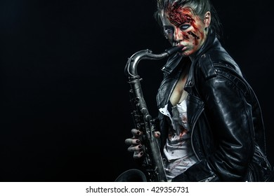 Horror. Dead musician, scary zombie playing on saxophone in halloween .