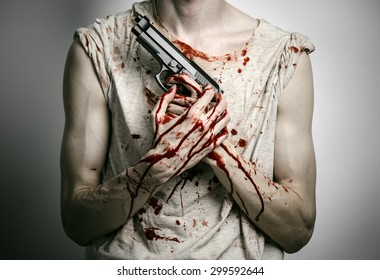 Horror and firearms topic: the bloody killer with a gun on a gray background in the studio