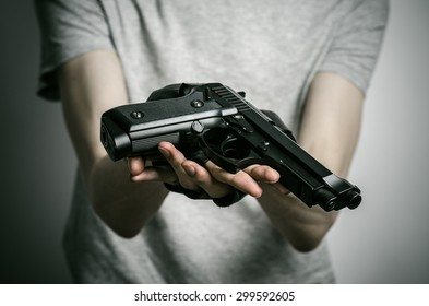 Horror and firearms topic: the killer with a gun on a gray background in the studio