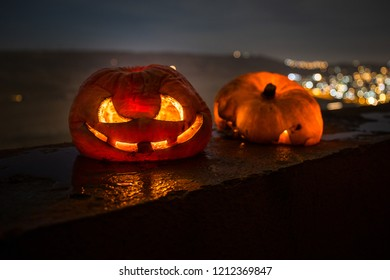 Horror Halloween concept. Close up view of scary dead Halloween pumpkin glowing at dark background. Rotten pumpkin head. Selective focus
