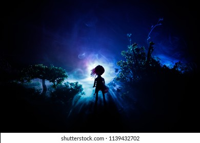 Horror Halloween decorated conceptual image. Alone girl with the light in the forest at night. Silhouette of girl standing between trees with surreal light on background. Selective focus.