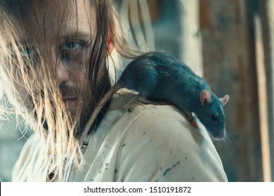 Horror For Halloween Holiday Crazy Man In A Dirty Measuring Shirt In An Old Ruined House Is Locked And Scares Everyone Surrounding Expecting A Victim With Rat