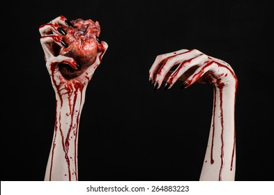 horror and Halloween theme: Terrible bloody hands with black nails holding a bleed human heart on a dark background isolated in studio