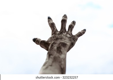 Horror and Halloween theme: Terrible zombie hands dirty with black nails reach for the sky, walking dead apocalypse, first-person view