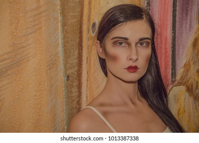 Horror make up. Beautiful girl in the corridor. Makeup at the beautiful brunette. Girl with long hair