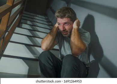 horror movie style portrait of sad and desperate man suffering depression problem or mental disorder sitting on staircase at home hopeless crying overwhelmed and helpless