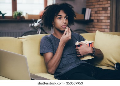 Horror movie. Young African man watching TV and looking scared while eating popcorn sitting on the couch at home