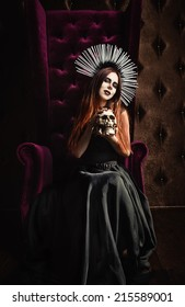 Horror photo: a beautiful gothic girl in black dress holds the skull