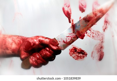 Horror photo of a killer bloody hand with sharp kitchen knife behind a blurred glass with bloody handprint on it.