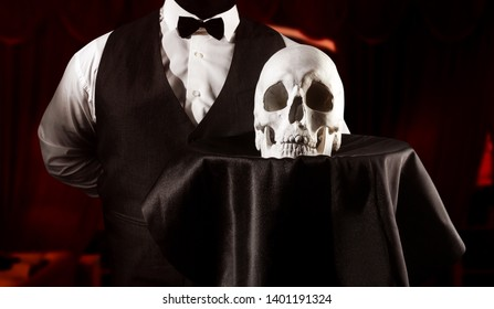 Horror photo of a waiter in white shirt and black waistcoat holding serving dish with skull on shaded red restaurant background torso view.