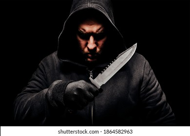 Horror scary photo of a dangerous creepy man in hoodie holding big hunting knife.