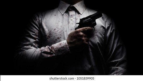 Horror scary photo of a killer in white shirt with blood splatter and posing with black gun on dark background.