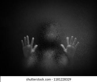 Horrorschatten von Frauen hinter Glas in Schwarz-Weiß. Unscharfe Geister oder Tote in der Dunkelheit. Stressartiges Mädchen, das im Zimmer gefangen ist, Konzept von Halloween oder Gewalt gegen Kinder.