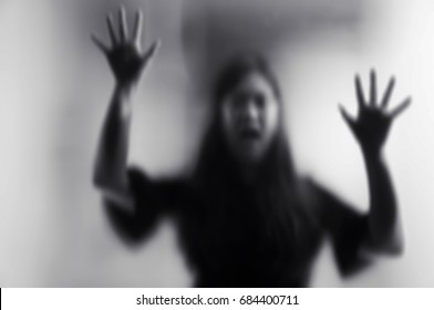Horror scary shadow of woman behind the matte glass in black and white. Blurry hand and body figure abstraction