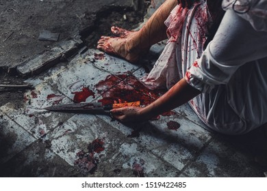 horror scence of women hold knife by hands with blood. Ghost women wear white dress stain blood at abandoned house. Halloween concept