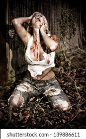 Horror scene of a bloody woman screaming in the woods by an old cabin