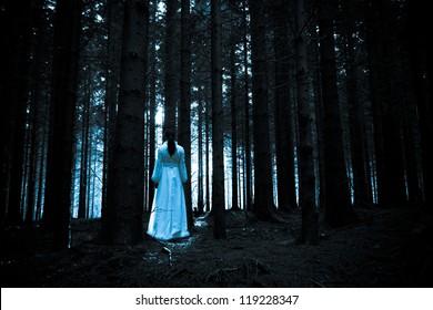 Horror Scene. Lady in white dress in a deep dark forest
