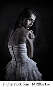 Horror Scene of a Possessed bride Woman black long hair ghost halloween in dark cage pound room. Portrait of bloody horrible scary zombie girl in a halloween festive makeup. holiday people concept.