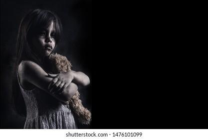 Horror Scene of a Possessed children girl black long hair hug doll ghost halloween in dark room