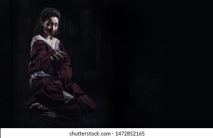 Horror Scene of a Possessed Woman sitting. ghost halloween in dark cage pound room banner. Portrait of bloody horrible scary zombie girl in a halloween festive makeup.