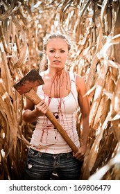 Horror Scene of a Pretty Blonde Woman Holding an Axe in a Corn Field