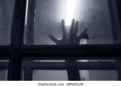 Horror scene of a scary hand on the window