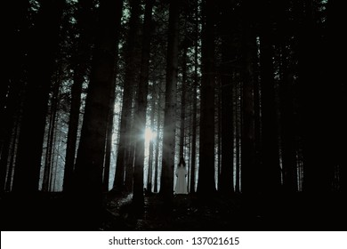 Horror scene of a scary woman - apparition of the female ghost in the deep spooky forest