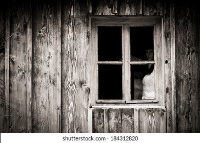 Horror scene of a scary woman. Mysterious woman staring out the window.