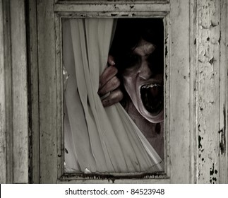 Horror Scene of a Scary Woman peeking out of a small window focus is on mouth