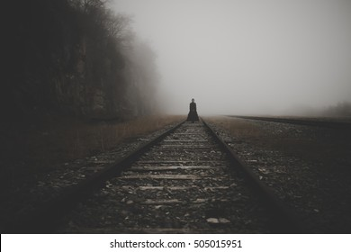 Horror scene of a scary woman standing on the trails surrounded by light fog